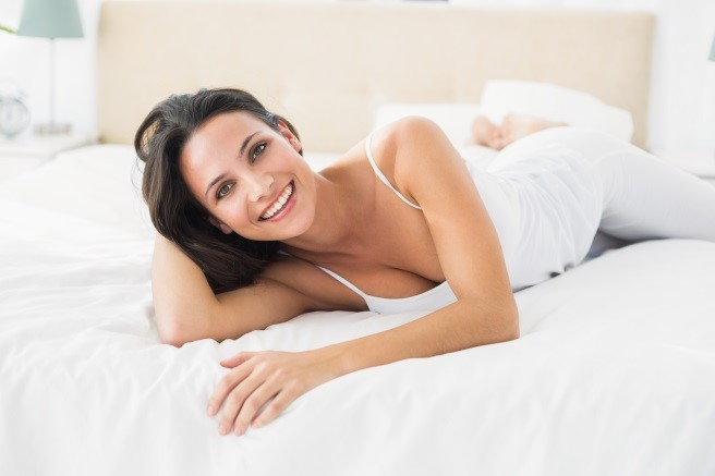 A woman smiling and lying on a bed