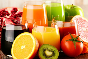 Glasses of fruit juice next to various pieces of fruit
